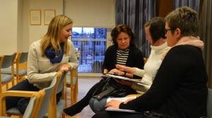 Fyra kvinnor pratar med varandra.