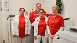 Personalen på en läkarcentral poserar i receptionen.