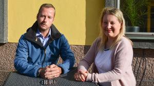 man och kvinna sitter vid ett bord framför en gul vägg
