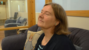 En kvinna sitter i en soffa och blundar.
