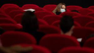 En kvinna omgiven av röda sammetsstolar i en biograf.