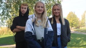 Tre ungdomar som ser in i kameran framför skolan i ett grönt höstigt landskap. Några höghus i bakgrunden.