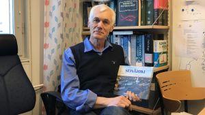 Forskaren Peter Bergsten vid Uppsala Universitet håller upp en bok med titeln Seinäjoki