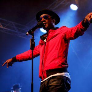 Aloe Blacc uppträder med hatt på huvudet och solglasögon och båda händerna utsträckta åt sidan.