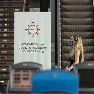 En resenär med munskydd går förbi en coronatestningsskylt på Helsingfors-Vanda flygplats.