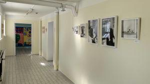 Fotografier på en grönvit betong vägg inne i en korridor.
