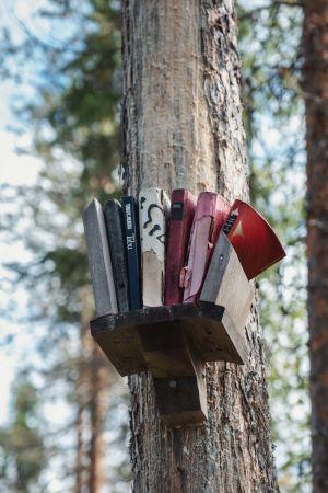 Puuhun naulattu hylly, jolla Timo K. Mukan kirjoja, selkämyksistä näkyy esim. Tabu