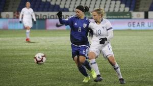 Två spelare, en vitklädd och en blåklädd, försöker nå en boll på en fotbollsplan.