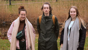 Tre personer, en pojke och två flickor, i en grupp i höstig miljö.