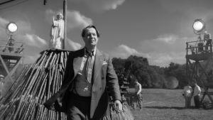 """På bilden bioplanschen för filmen """"Mank"""" som berättar historien om hur manuset till Citizen Kane blev till. Bilden är svartvit och man ser huvudpersonen spelad av Gary Oldman gå på en filminspelning, i bakgrunden syns en vitklädd kvinna."""