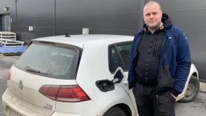 En man står intill sin vita bil med ett öppet tanklock.