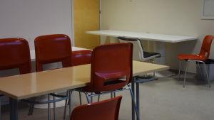 Ett beigefärgat, rektangulärt bord och röda plaststolar. I bakrunden ett vitt rektangulärt bord och flera stolar.