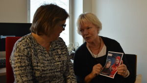 Siw Karlsson och Ulla-Stina Engström håller i en broschyr om Röda Korsets vänverksamhet.