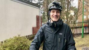 Anders Munck med cykelhjälm och cykel framför dagisgård.