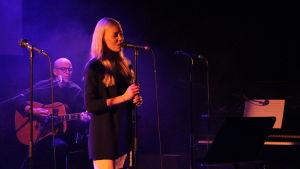 En blond kvinna sjunger på en scen. En man spelar akustisk gitarr.