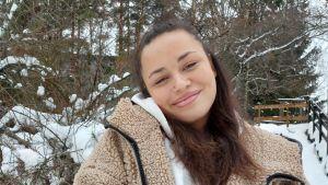 Kiara Nelson ser in i kameran, har lurvig jacka. Snö på träd i bakgrunden.