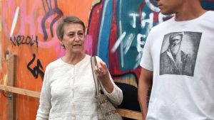 Kvinna i vit blus och med kort hår talar med en man i vit t-skjorta. I bakgrunden graffiti i olika färger.