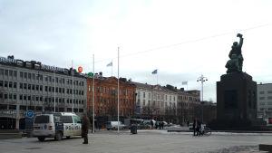 En ensam man står bredvid en polisbil på Vasa torg. Frihetsstatyn syns i bakgrunden.