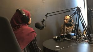 Två personer sitter framför mikrofoner i en poddstudio.