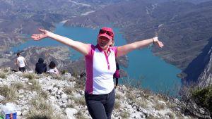 En kvinna står uppe på ett högt berg. Nedan syns en sjö.