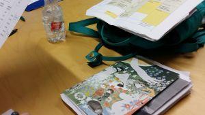 En skolväska och en anteckningsbok med Muminmotiv ligger på ett bord.