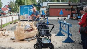 Mies ottaa kuvaa pienestä lapsesta, joka on veneen mallisessa puuveistoksessa