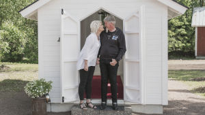 Nainen ja mies käsi kädessä pikkuruisen valkoisen puukirkon edessä.