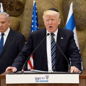 Donald Trump, med premiärminister Benjamin Netanyahu i bakgrunden talar vid Yad Vashem, monumentet och forskningscentret för förintelsens offer i Jerusalem 23.5.2017.