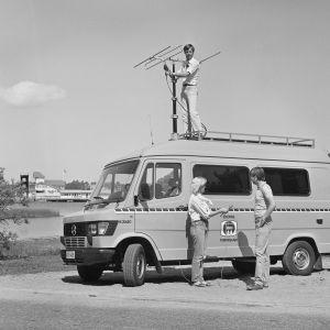 Två personer står vid en radiosändningsbil medan en tredje står på bilens tak.