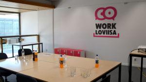 Ett kontorsrum med ett bord med läskedrycker på och en stor logga i rosa och svart på väggen