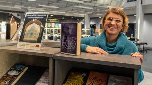 Malin Hollmén vid en bokhylla.