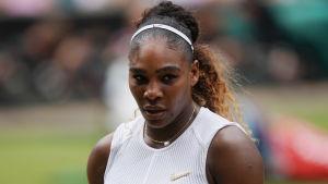 Serena Williams håller i sin racket och tittar nedåt.