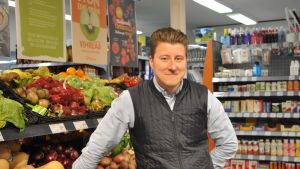 Kristian Eklund står vid fruktdisken inne i sin affär i Korpo.