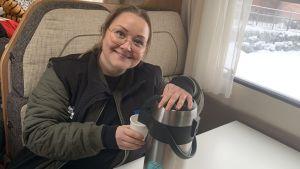 En kvinna tappar upp kaffe ur termos i en mugg i en husbil.