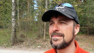 Mikael Sarelin, en man med orange tröja, skägg, mustasch och skärmmössa.