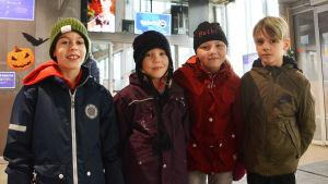 Fyra barn i ytterkläder tittar ini kameran.