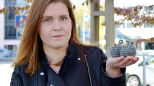 Cassandra Lindén håller i två virkade bollar som ser ut som getingbon.