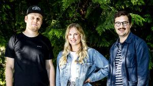 Tre personer står framför ett grönt buskage.