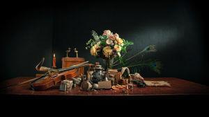 Viulu, kukkia, kortteja, kynttilä ynnä muuta sekalaista tavaraa asetelmana pöydällä. Kuva dokumenttielokuvasta Neiti Aika.