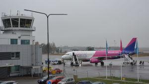 Wizz airs flyg i vitt, rosa och blått har landat på Åbo flygplats och folk håller på att stiga ur planet.