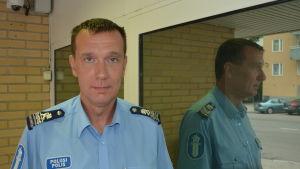 En man med polisskjorta på står framför en dörr.