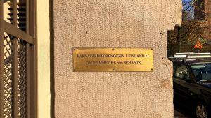 En mässingsskylt på en beige stenvägg.