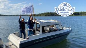 Matias och Micke vinkar från båten.