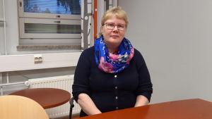 Portättfoto av en kvinna som sitter vid ett bord och ser in i kameran.