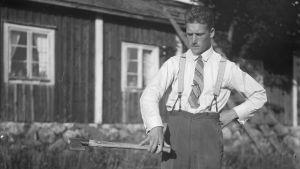 En man lyfter en yxa. Bilden är tagen 1930 i Bromarf.