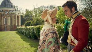 Söta Sophia och stiliga Edmund i en parkilknande miljö med en vacker byggnad i bakgrunden.