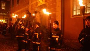 Fem unga män eller pojkar i den frivilliga brandkårens kläder står och håller i brinnande facklor framför ett hus.
