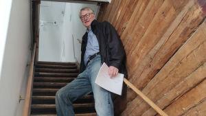 En äldre man står uppe i en trappa och tittar neråt.