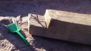 Spikar sticker upp ut söndrig sandlåda