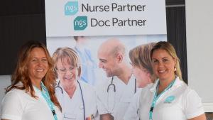 Paula Agge och Sanna Pöyhölä som jobbar med rekrytering av sjukskötare  poserar vid företagets reklamplansch.